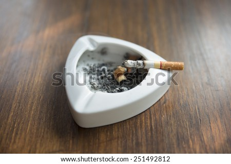 white ashtray with cigarette butts wooden table