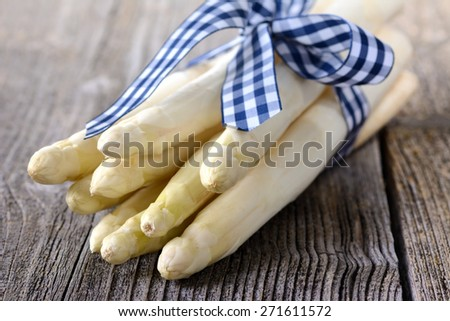 White asparagus of Germany (Bavaria) with a blue and white checkered ribbon on a wooden table - stock photo