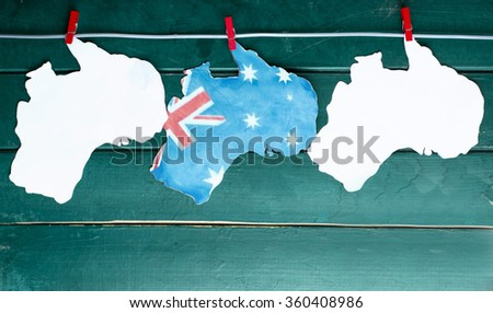 White Australian maps and flag hanging pegs ( clothespin ) on a line against a blue background. Space for text, Australia collage, toned image