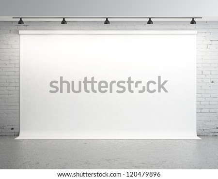 White backdrop in room with brick wall - stock photo