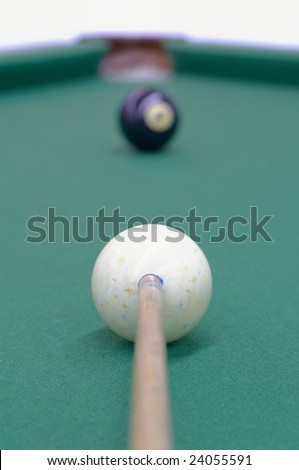 white ball, black ball and the billiard-pocket are on the same line providing the good opportunity to win the game; focus on the point where the cue touches the white ball - stock photo