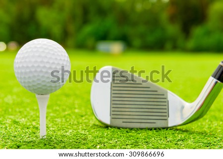 White ball on tee and golf club on the field - stock photo