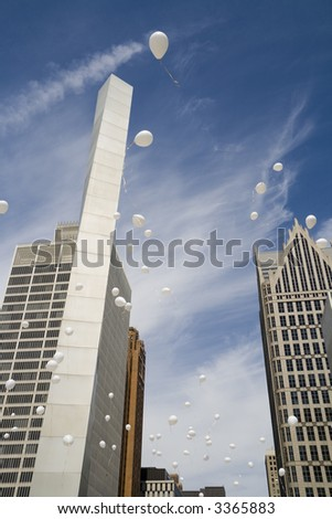 White balloons released simultaneously in downtown Detroit - stock photo
