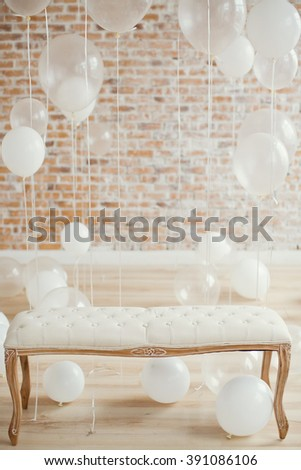 white baloons with bench and brick wall on background