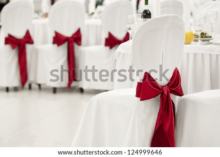 White banquet chair with a red bow in the banquet hall - stock photo