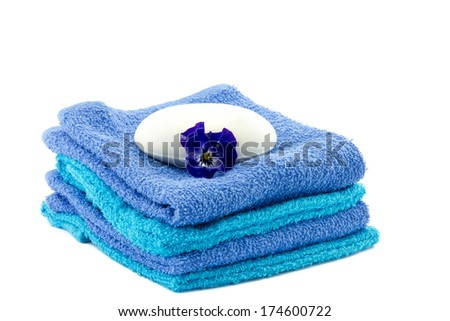 white bar of soap on blue piled towels and pansy flower next to it - stock photo