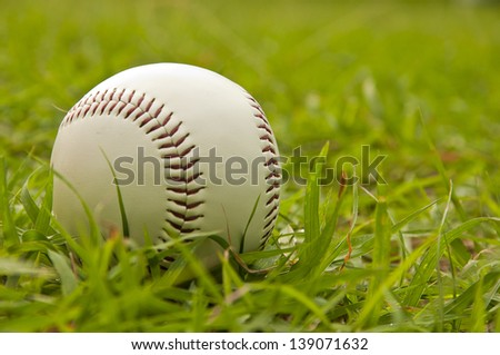 white baseball on the green grass - stock photo