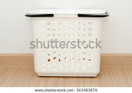white basket on floor in room. - stock photo