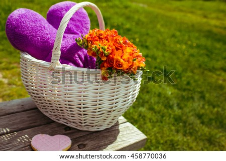 White basket with violet toy and orange bouquet stands on the bench