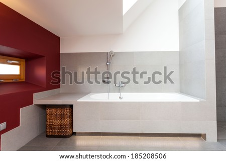 White bath in modern bathroom with red wall - stock photo