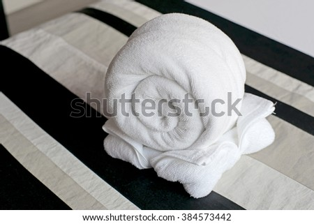 white bath towels rolled and piled on the bed