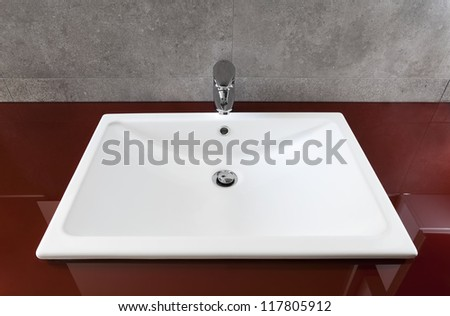 White bathroom sink on a red translucent board - stock photo