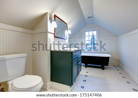 White bathroom with vaulted ceiling. Antique style bath tub, green wood cabinet accomplish old-style theme - stock photo