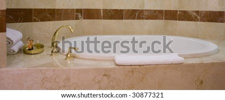 White bathtub and brass taps decorated with marble tiles - stock photo
