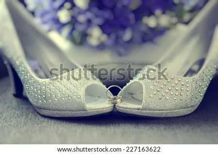 White beaded shoes of bride with wedding rings
