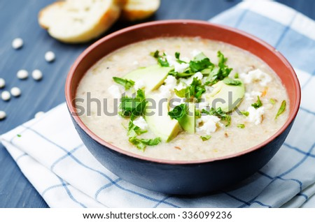 White beans chicken soup on a dark wood background. toning. selective focus