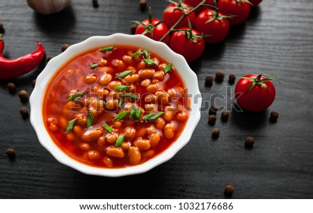 white beans in tomato sauce in a white bowl on dark wooden background