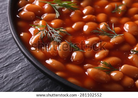 white beans in tomato sauce with dill in a black bowl close-up. horizontal - stock photo