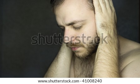white bearded man closing his ears with hands