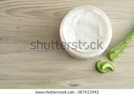 White beauty cream in a jar displayed with aloe Vera on a wooden background - stock photo