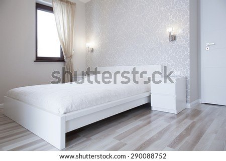 White bed in bright bedroom in apartment - stock photo