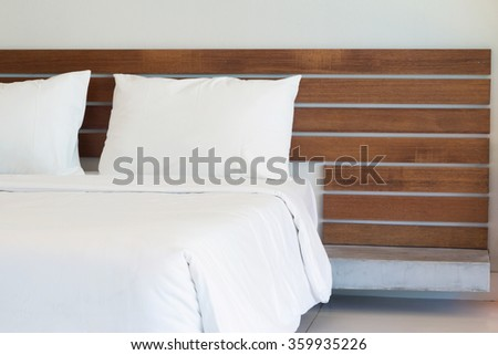 white bedclothes with wood headbord. - stock photo