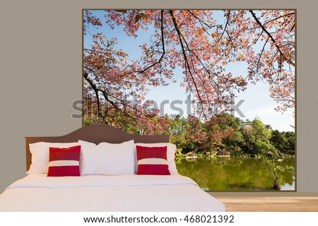 White bedding sheet and pillows on the bed in a room with big window see through lake and forest view as background
