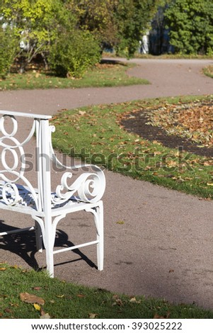 white bench in park with a grass and flowers behind - stock photo