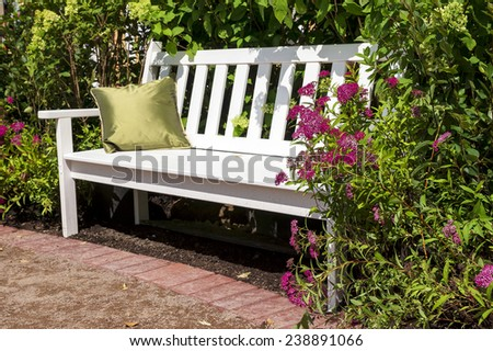 white bench in the lush garden - stock photo
