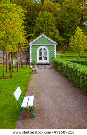 White benches and small green wooden house in beautiful park