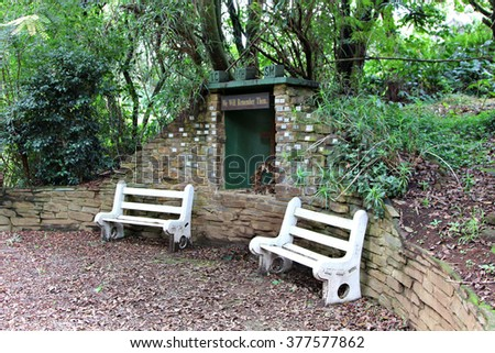White benches in a restful garden of remembrance against a stone wall. - stock photo