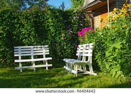 White benches in a secluded corner of lush green garden - stock photo