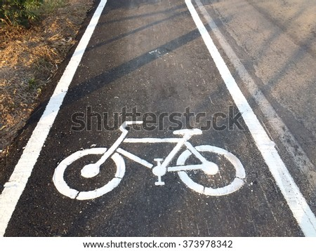 White bicycle sign on asphalt bike lane parallel car road - stock photo