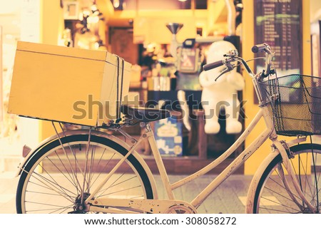 White bicycle with a yellow box in back seat parked in front of a cafe. Retro effect. - stock photo