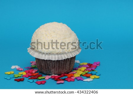 white birthday cupcake with colorful decoration on blue background - stock photo