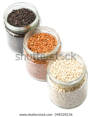 White, black and brown millet grain seed in mason jar over white background
