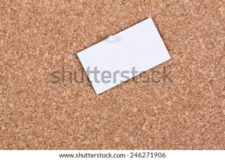 White blank business card attached to a cork board - stock photo