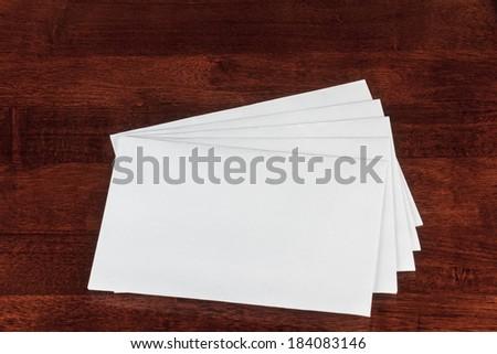White Blank Envelopes on a Dark Brown Table - stock photo