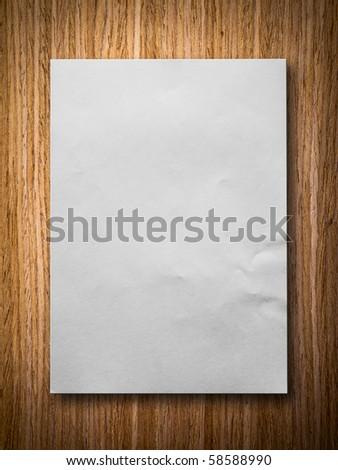 white blank paper on oak wood background - stock photo