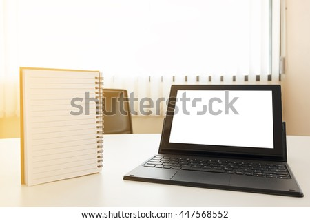 white blank screen computer tablet and notepad on office table