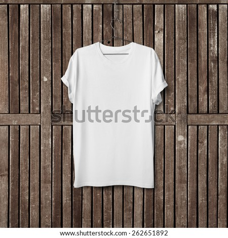 White blank t-shirt on wood wall - stock photo