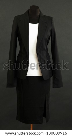White blouse and black skirt with coat on mannequin on black background
