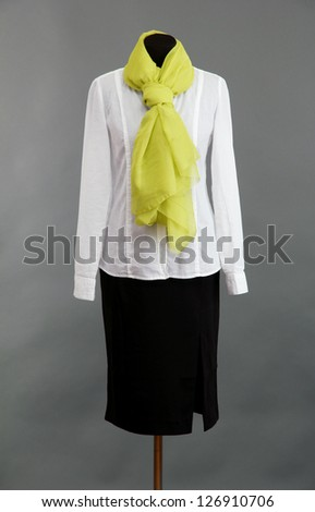 White blouse, black skirt and green scarf on mannequin on grey background