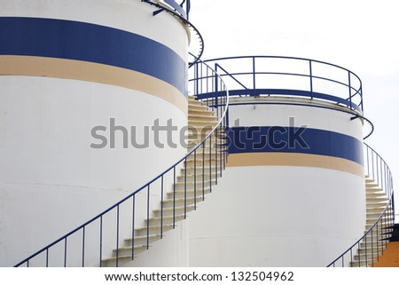 white blue and yellow fuel tank made with cement - stock photo