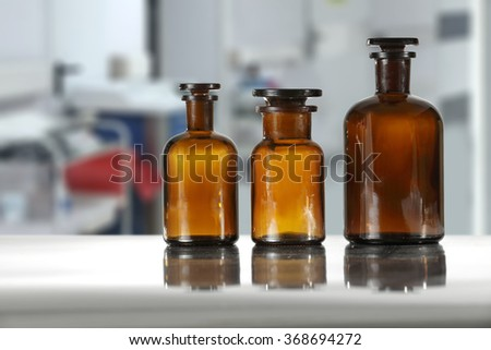white blurred background of hospital interior and shelf of brown bottles