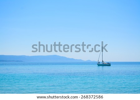 white boat alone in the sea on a clear summer day - stock photo