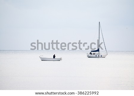white boats in a white sea under a white sky - stock photo