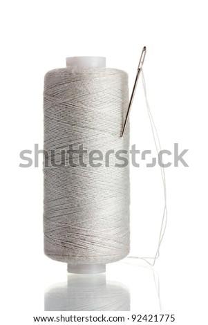 White bobbin with needle isolated on white - stock photo