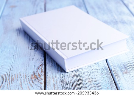 White book on wooden table - stock photo