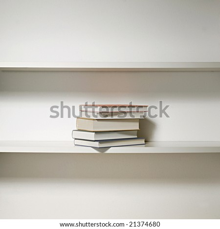 white bookshelf in three rows with few books in the middle - stock photo